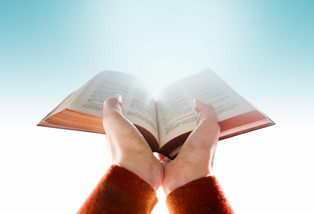 Mãos de mulher levantar uma bíblia para rezar Foto Premium