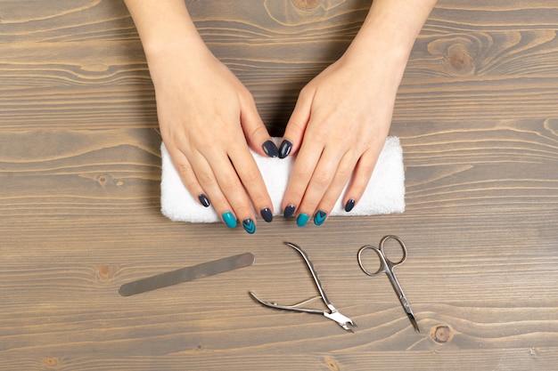 Mãos de mulher recebendo uma manicure em salão de beleza Foto Premium