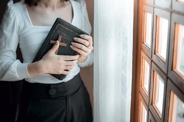 Mãos de mulher rezando com a bíblia e uma cruz de madeira na igreja Foto Premium