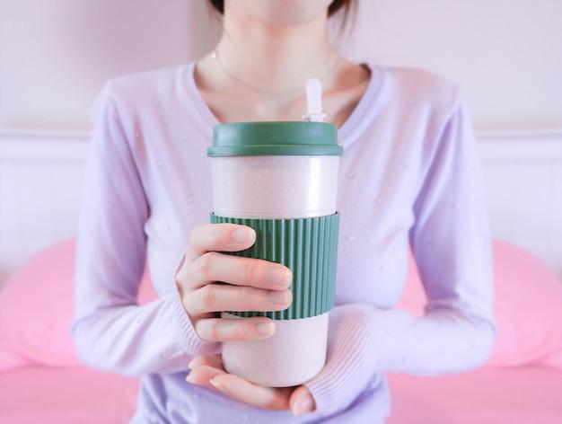 Mãos de mulher segurando a xícara de café. menina na camisola segurando caneca. Foto Premium