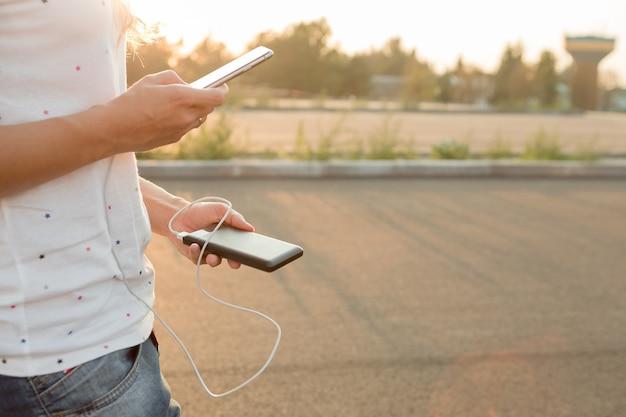 Mãos de mulher segurando um smartphone preto, carregando a bateria do banco de potência externa Foto Premium