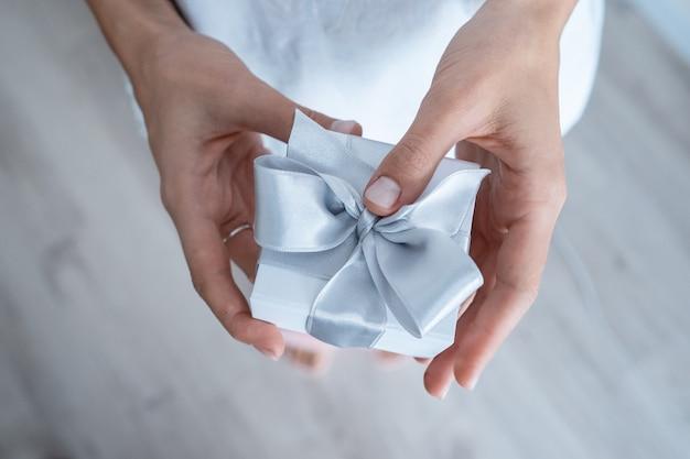 Mãos de mulher segurando uma caixa de presente com laço branco, close-up Foto gratuita