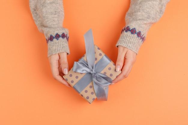 Mãos de mulher segurando uma caixa de presente em laranja Foto Premium