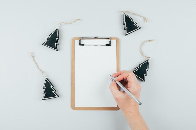 Mãos de mulher segurando uma folha de papel ou caderno e caneta. mesa cinza. vista do topo. conceito de maquete Foto Premium