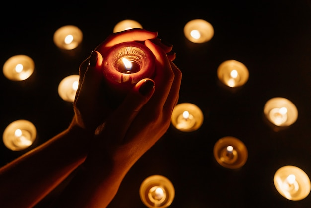 Mãos de mulher segurando uma vela acesa. muitas chamas de velas brilhando. fechar-se. Foto Premium