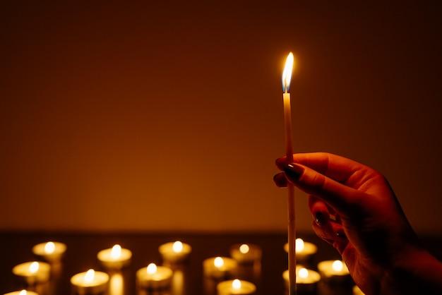 Mãos de mulher segurando uma vela acesa. muitas chamas de velas brilhando. Foto Premium