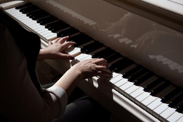 Mãos de mulher tocando um piano, instrumento musical. Foto Premium