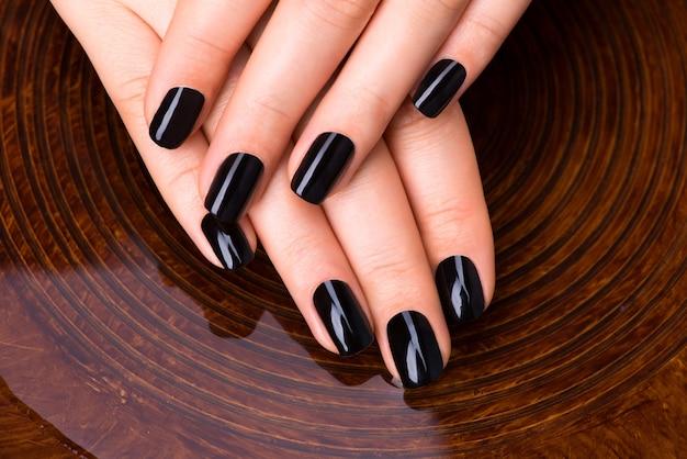 Mãos de mulheres bonitas com manicure preta após procedimentos de spa - conceito de tratamento de spa Foto gratuita