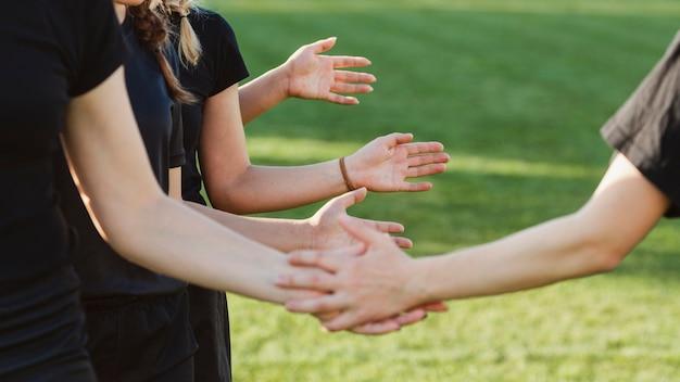 Mãos de mulheres saudando antes de uma partida Foto gratuita