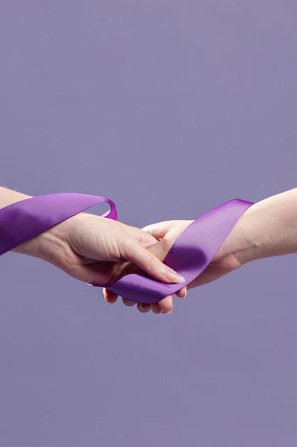 Mãos de mulheres segurando uma fita com espaço de cópia Foto gratuita