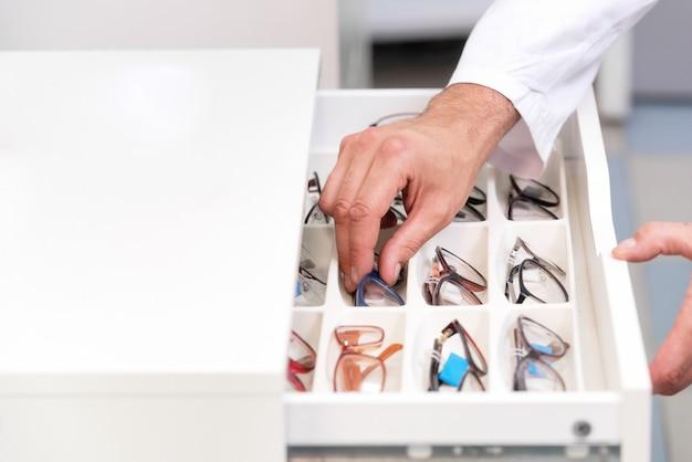 Mãos de oftalmologista close-up, escolhendo óculos de uma gaveta na loja óptica Foto Premium
