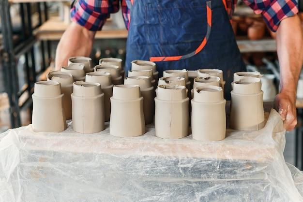 Mãos de oleiro masculino segurando a bandeja com potes de cerâmica em cerâmica. Foto Premium