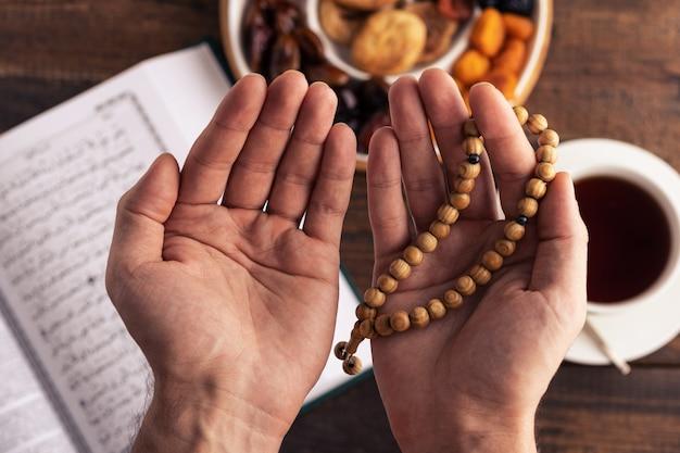 Mãos de oração com rosário de madeira no fundo do livro alcorão, xícara de chá, prato de frutas secas, conceito iftar, mês do ramadã, vista superior, closeup Foto Premium