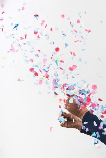 Mãos de pessoa e confetes coloridos Foto gratuita