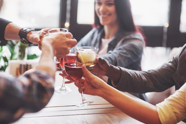 Mãos de pessoas com copos de uísque ou vinho, comemorando e brindando Foto Premium