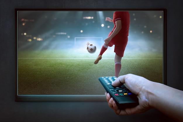 Mãos de pessoas com remoto assistindo jogo de futebol Foto Premium