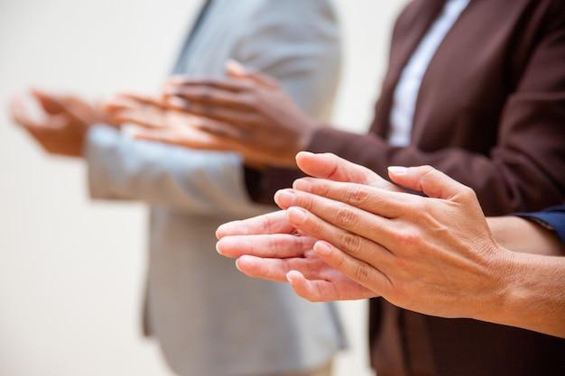 Mãos de pessoas de negócios aplaudindo orador Foto gratuita