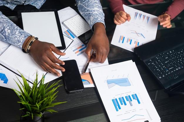 Mãos de pessoas de pele escura trabalham com tablet de documentos financeiros no espaço de negócios closeup Foto Premium