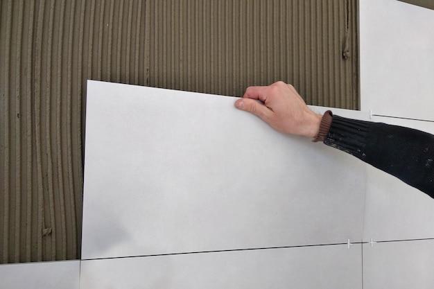 Mãos de trabalhador colocando telhas cerâmicas. Foto Premium