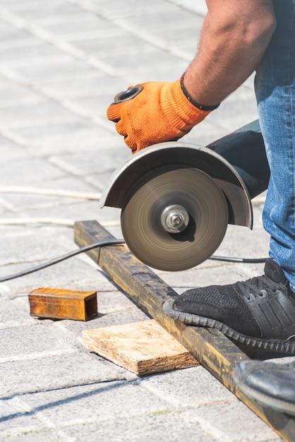 Mãos de trabalho corta um tubo de metal com rebarbadora Foto Premium