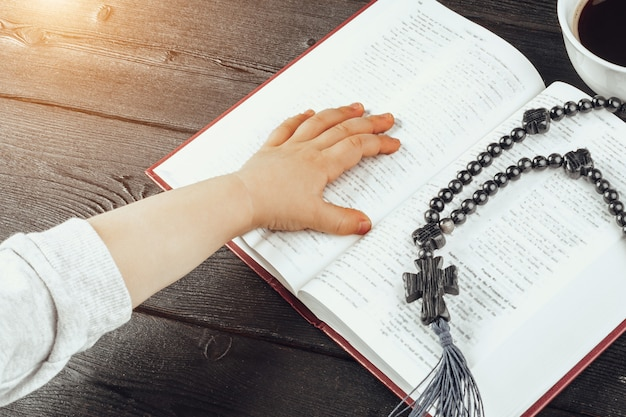 Mãos de um jovem cristão e bíblia sagrada na mesa de madeira Foto Premium