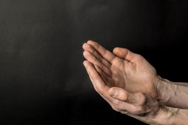 Mãos de um muçulmano rezando em um fundo preto. Foto Premium