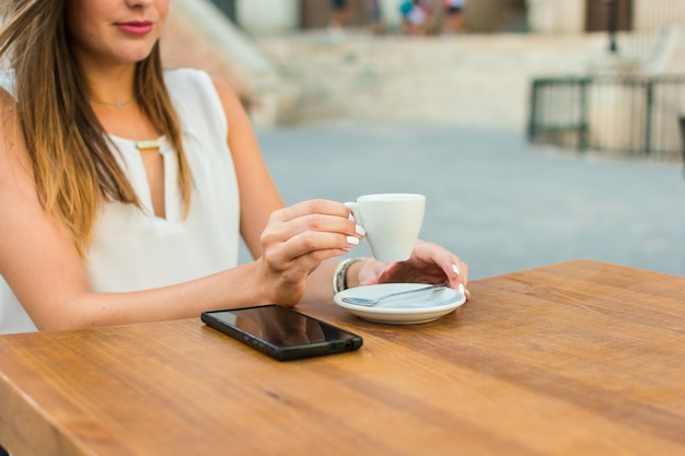 Mãos, de, um, mulher jovem, é, segurando, um, xícara café, ligado, um, terraço, de, um, bar Foto Premium