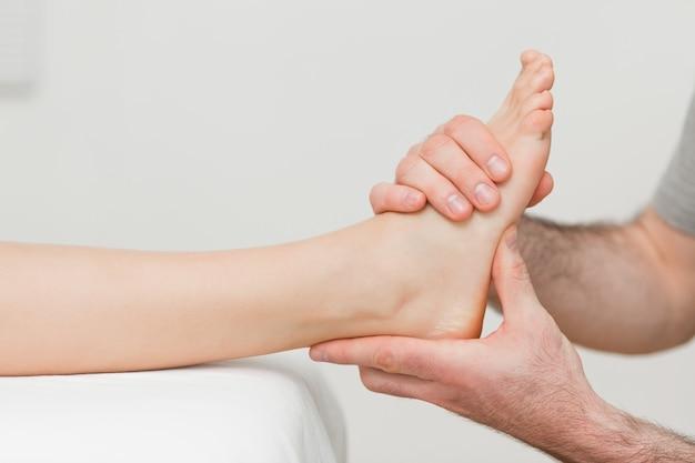 Mãos de um osteopata que faz massagens um pé Foto Premium