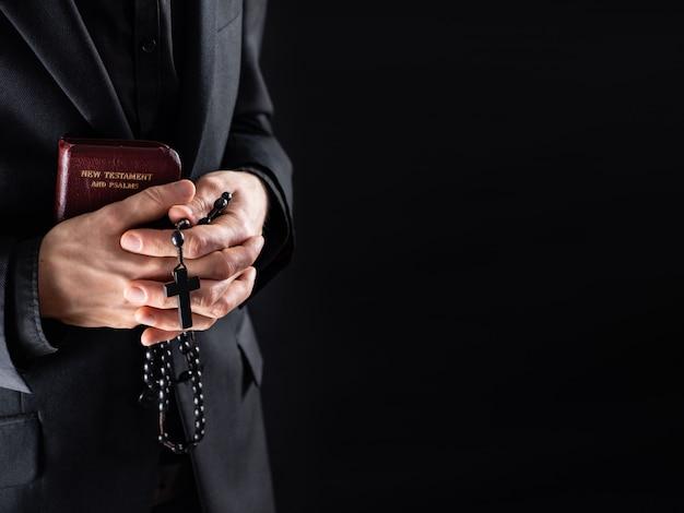 Mãos de um padre cristão vestida de preto, segurando um crucifixo e um livro do novo testamento. pessoa religiosa com grânulos da bíblia e de oração, imagem discreta com espaço de cópia. Foto Premium