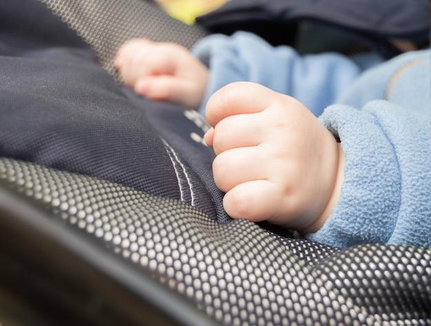 Mãos de um punho de bebê, foco seletivo, a criança está no carrinho Foto Premium