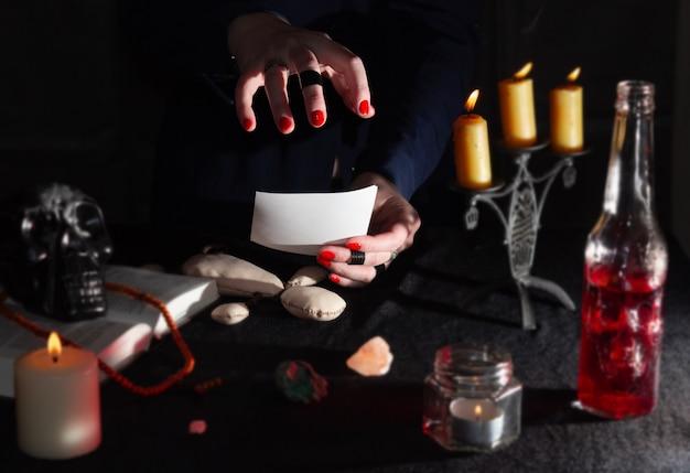 Mãos de uma bruxa em um ritual fotográfico e parafernália Foto Premium