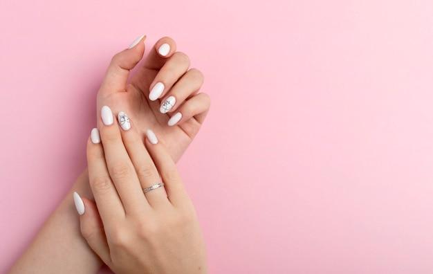 Mãos de uma linda mulher bem cuidada com unhas femininas em um fundo rosa. manicure, pedicure conceito de salão de beleza. espaço vazio para texto ou logotipo. nas unhas esmalte de gel branco com um abstrato Foto Premium