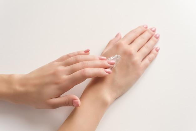 Mãos de uma mulher aplicar creme branco Foto Premium