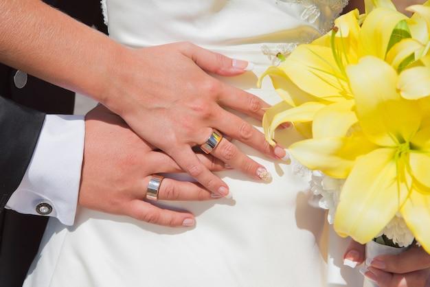 Mãos de uma noiva e do noivo com anéis de casamento e buquê de lírios amarelos Foto Premium