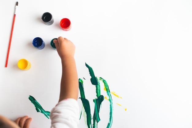 Mãos de uma pintura do rapaz pequeno com as aquarelas na folha do livro branco. garotinho com um pincel e tintas. Foto Premium