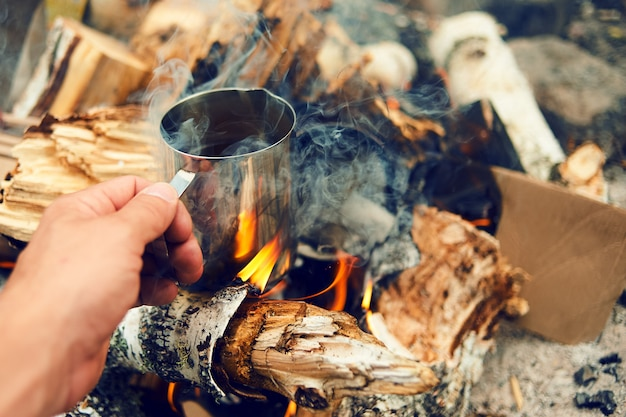 Mãos de viajante homem segurando uma xícara de chá perto do fogo ao ar livre. alpinista bebendo chá da caneca no acampamento. café cozido sobre uma fogueira na natureza. conceito de aventura, viagens, turismo e camping. Foto Premium