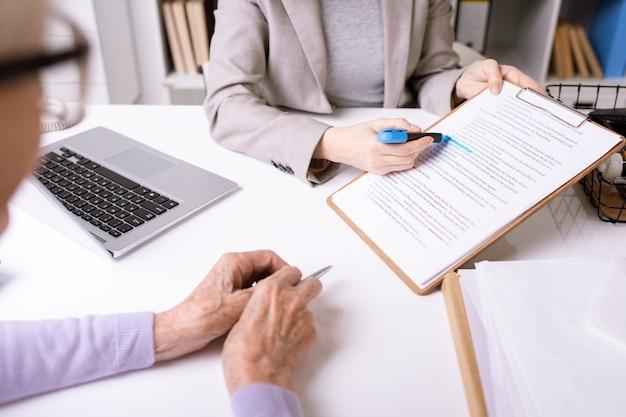 Mãos do agente de seguros sublinhando a frase importante no documento por um marcador azul enquanto a explica ao cliente sênior Foto Premium