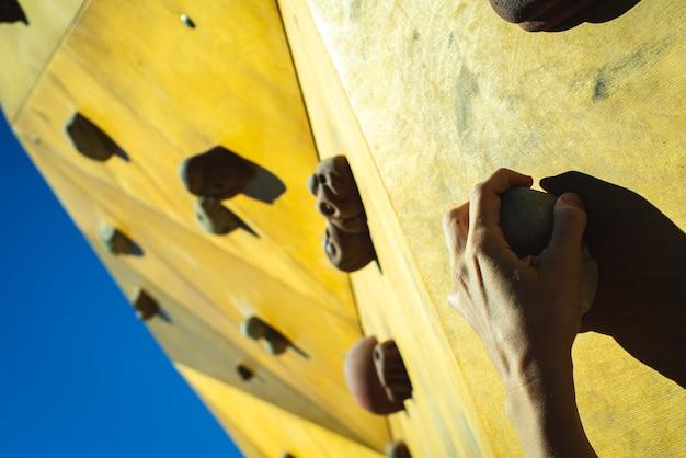 Mãos do alpinista presas aos suportes de uma parede de escalada ao ar livre. Foto Premium