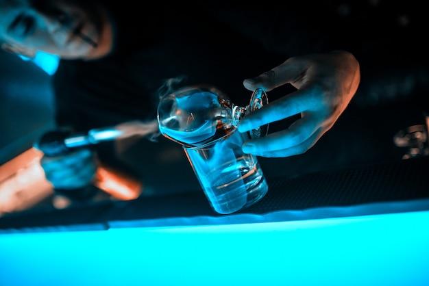 Mãos do barman, taça de vidro no balcão do bar Foto Premium