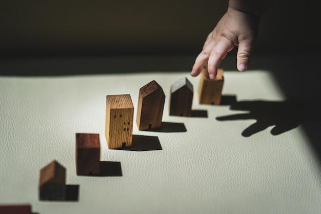 Mãos do bebê que escolhem o mini modelo da casa de madeira. o conceito de relocação, hipoteca Foto Premium