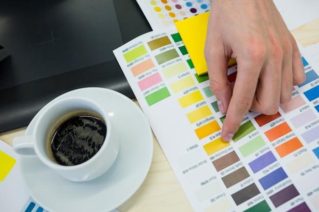 Mãos do desenhador gráfico a cores do sexo masculino escolher entre cartela de cores Foto gratuita