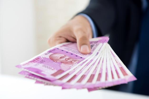 Mãos do empresário segurando dinheiro, moeda da rúpia indiana Foto Premium
