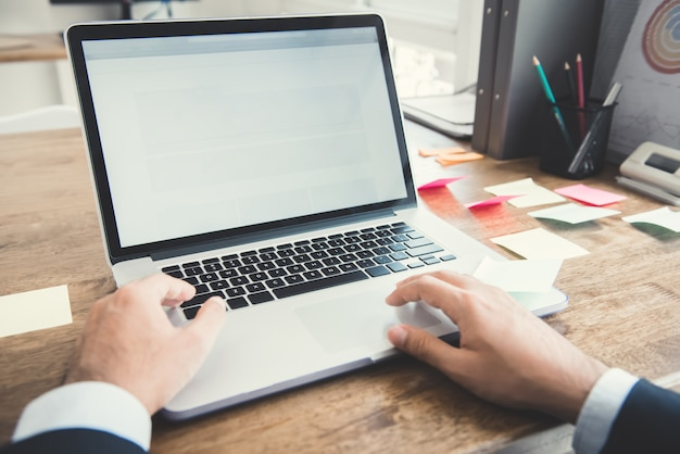 Mãos do empresário usando computador notebook na mesa de trabalho no escritório Foto Premium