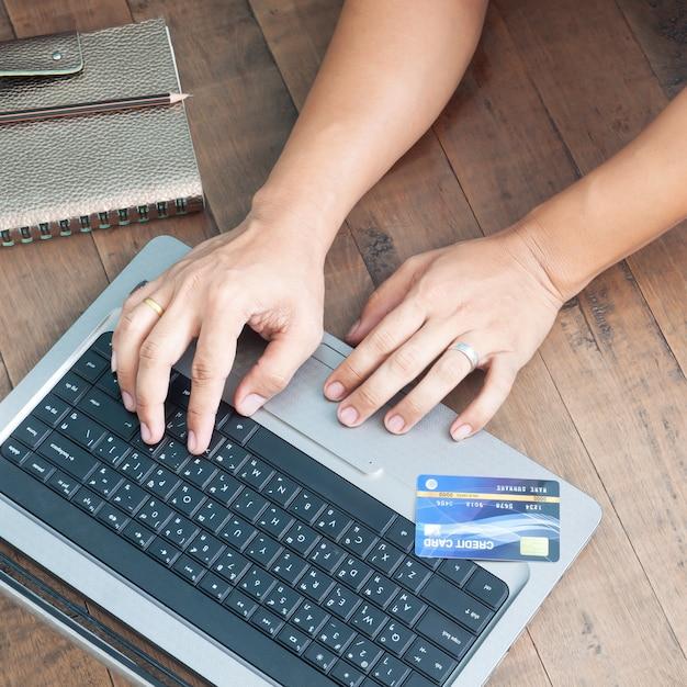 Mãos do homem usando o portátil e o cartão de crédito. compras online. Foto Premium