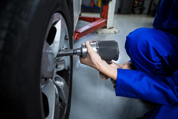 Mãos do mecânico fêmea que fixa uma roda de carro com chave pneumática Foto gratuita