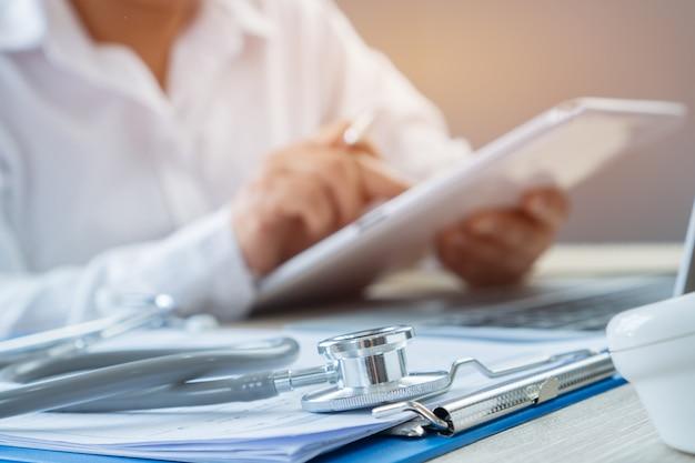 Mãos do médico escrevendo e trabalhando por caneta para medicação de ordem no tablet Foto Premium