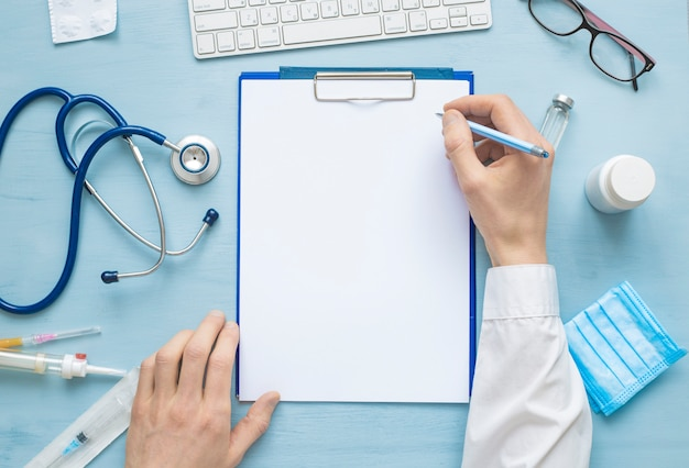 Mãos do médico escrevendo uma prescrição ou relatório médico em uma folha de papel em branco. Foto Premium