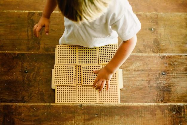 Mãos do menino que manipulam contando cubos no fundo de madeira na sala de aula montessori Foto Premium