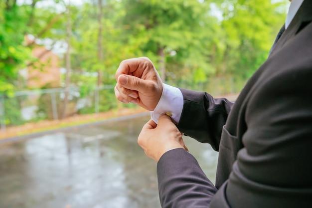 Mãos do noivo do casamento se preparando no terno Foto Premium