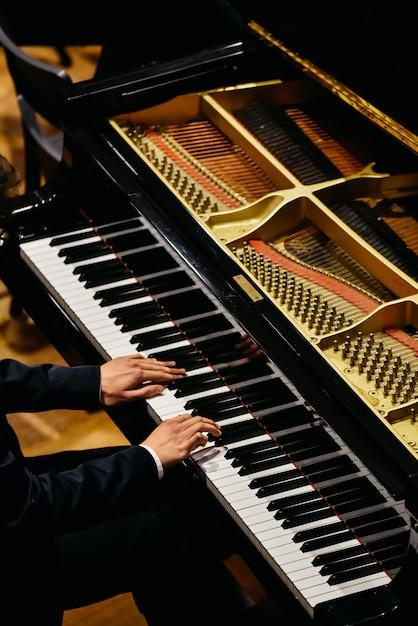 Mãos do pianista clássico que jogam seu piano durante um concerto. Foto Premium